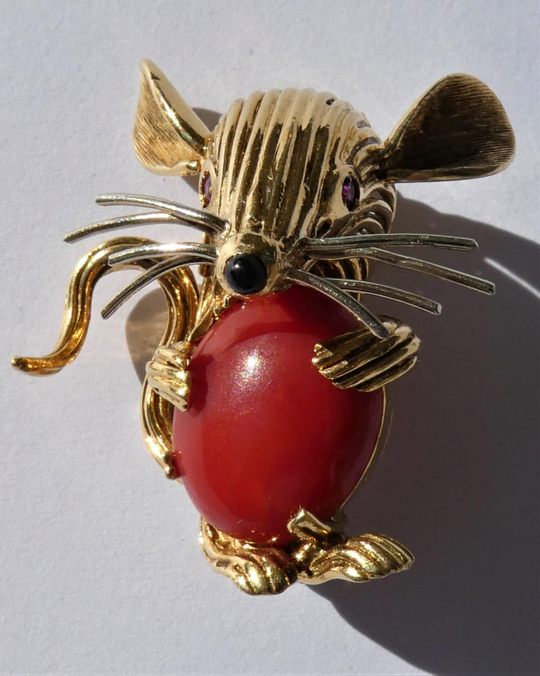 This lovely mouse brooch was crafted in Italy in the 1950s in 18 karat yellow gold. It has wonderful details like a chubby belly made out of a dark red Mediterranean coral cabochon and a black onyx nose. The mouse has 2 round cut vibrant red ruby