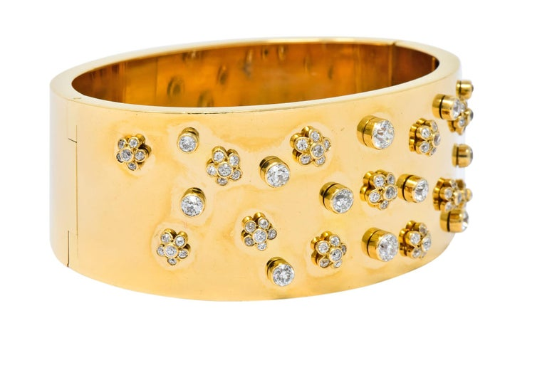 Wide bangle style gold bracelet with a high polished finish  Set to front with old European cut diamonds weighing approximately 2.28 carats total, H/I color and VS clarity  Bezel set in floral motifs with single stone accents  Completed by concealed