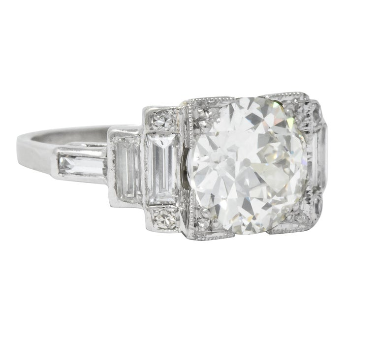 Centering an old European cut diamond set in a square form head weighing 2.84 carats, L color and VS1 clarity  Flanked by bezel set baguette cut diamonds in stepped design with bead set single cut diamond accents weighing approximately 0.45 carat