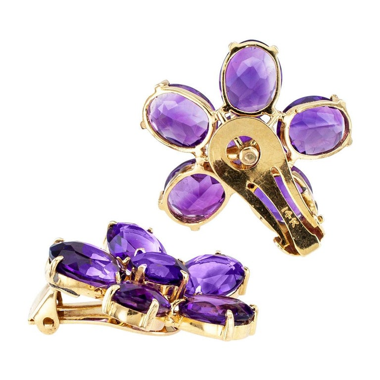 Retro amethyst and gold earrings circa 1950. Designed as flowers comprising petals formed by five oval-shaped amethyst encircling a single round amethyst, mounted in 14-karat yellow gold, the amethyst totaling approximately 25.00 carats, clip backs.