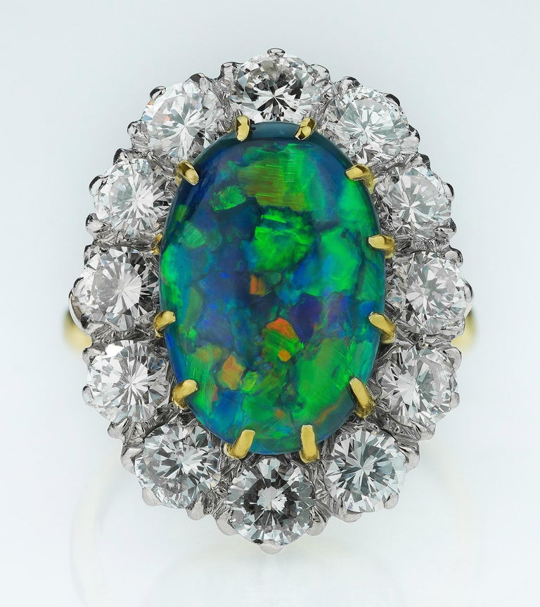 Australian black opal and diamond cluster ring in 18K white and yellow gold.  1 x Cabochon black opal, approximate weight 4.0 carats 12 x round brilliant cut diamonds, approximate total weight 2.2 carats, assessed colour I/J, assessed clarity