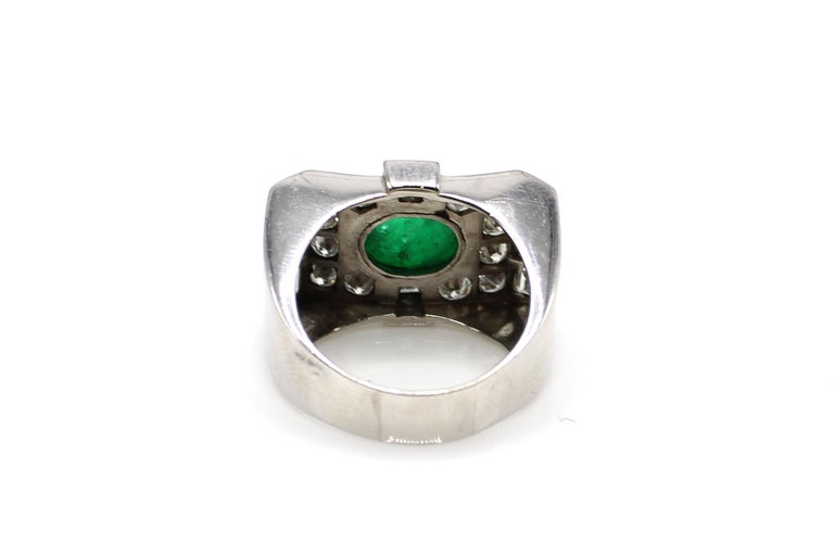 This bold statement ring is centrally set with a lovely deep green cabochon emerald measured to weigh  approximately 3 carats. Surrounding the bezel set emerald are  8 baguette and 12 bright white sparkly round diamonds totaling approximately 2.5