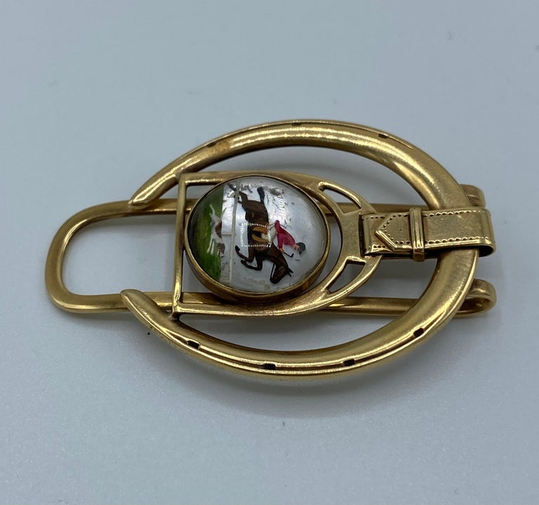Product details:  The money clip is designed by Cartier in the 1940's. It is made out of 14 karat yellow gold, enamel cover with rock crystal over it. It features horseshoe and man on the horse, equestrian motif.