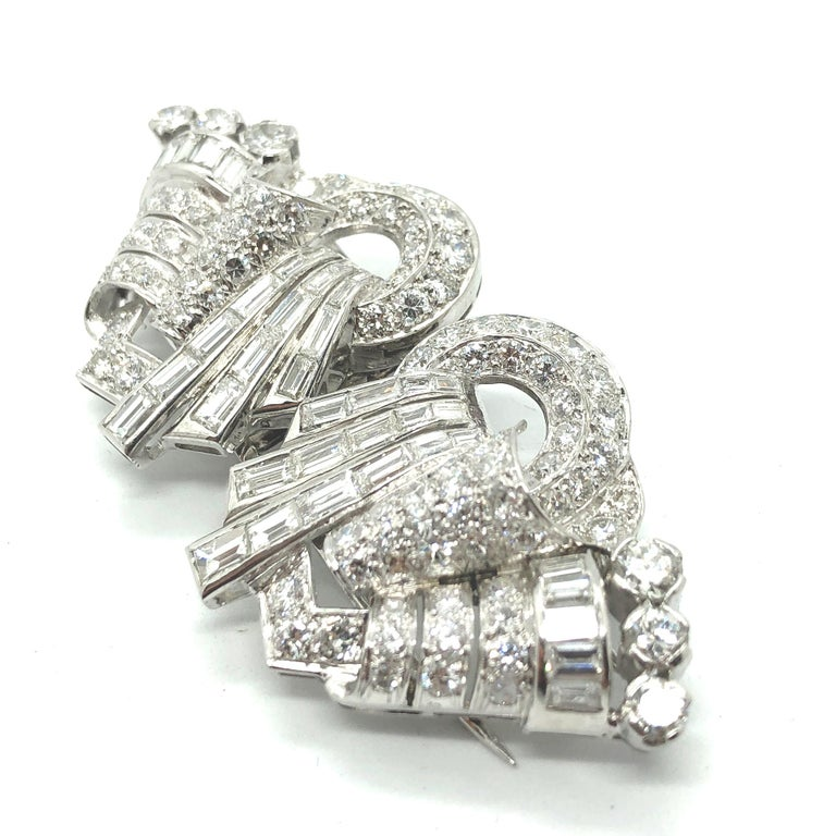 A diamond double clip brooch in platinum, Art Deco, ca. 1940s. The clips are set with round brilliant cut diamonds and diamond baguettes, following a very artistic design. The total diamond weight is circa 10 carats of very fine quality diamonds E/F