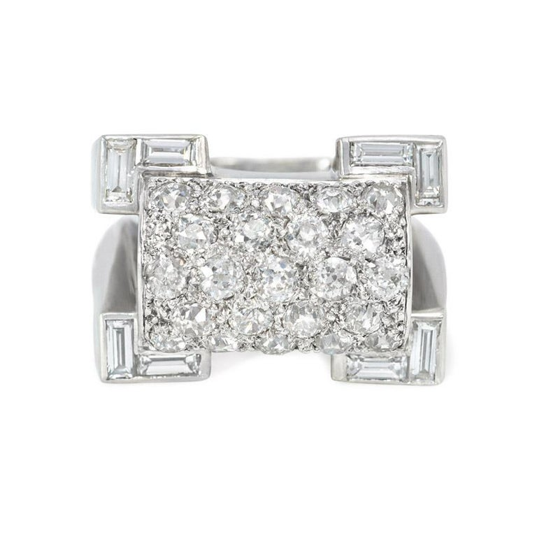 A Retro odeonesque platinum, gold, and diamond ring of geometric design, featuring a pavé diamond-set half-cylindrical center with re-entrant corners set with baguettes, in 18k and platinum.  French import.  Atw 2.94 cts.  Face-up dimensions: 17mm x