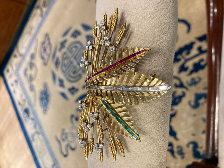 A beautiful retro clip brooch of wheat design,  in 18 karat yellow gold with diamonds, rubies, and emeralds. Circa 1940.