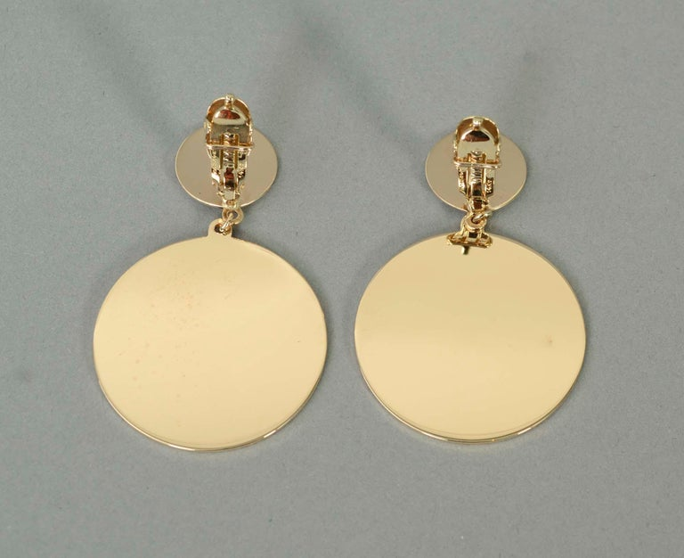 Retro earrings of two circular discs. The top one measures half an inch in diameter; the bottom one is 1  5/16