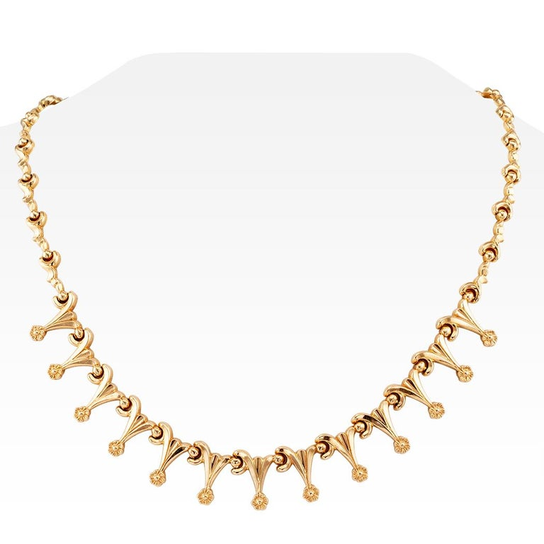 Retro gold fringe necklace circa 1950. Crafted in 18-karat gold as a series of elongated, interlocking links, decorated to the front with a complimentary fringe motif, each fringe terminating upon a single flower. We love the daintiness and
