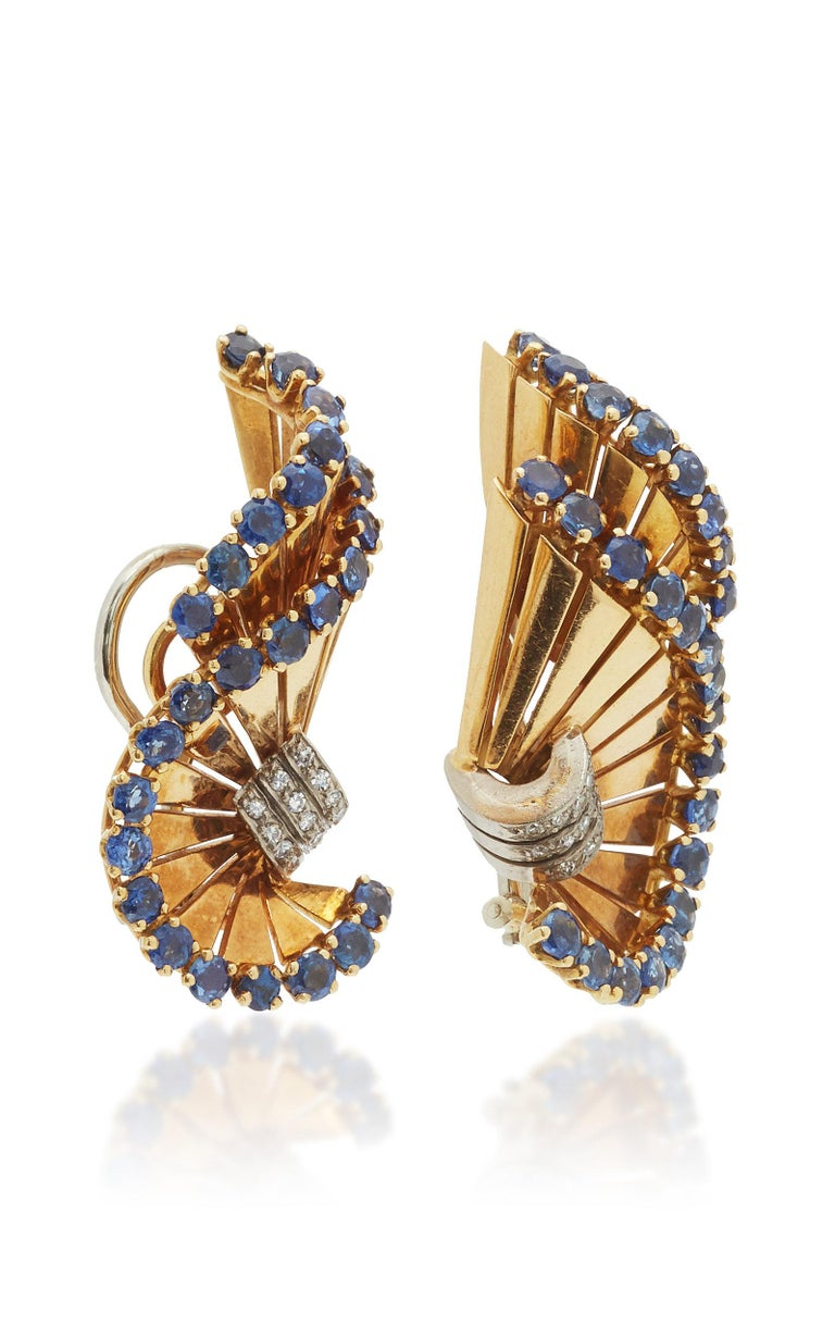 A pair of Retro 18kt yellow gold ear-clips of swirl design, embellished with sapphires and diamonds. By Gubelin, made in Switzerland, circa 1955.