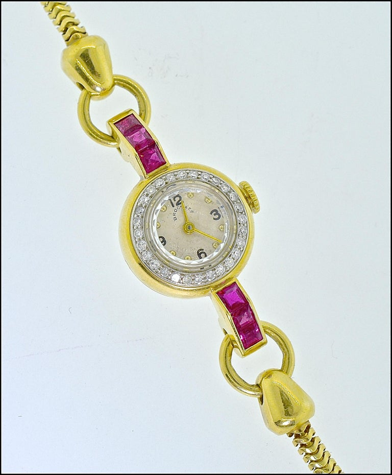 Retro vintage ladies wrist watch  by Brock, this watch   has a strong retro, Art Moderne, design. There are 6 fine natural rubies, probably unheated Burma stones, as evident of their fine  color.  There are diamonds surrounding the diamond.  The 17
