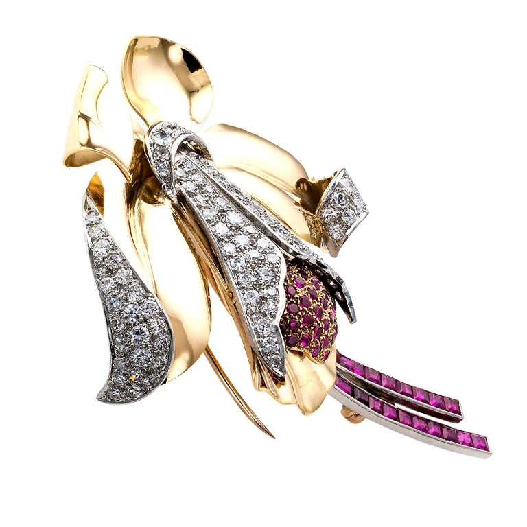 Retro diamond ruby gold and platinum orchid clip brooch circa 1940.  DETAILS:  DIAMONDS: ninety-seven round diamonds totaling approximately 3.00 carats, approximately H – I color and VS – SI clarity.  GEMSTONES: fifty-six rubies weighing