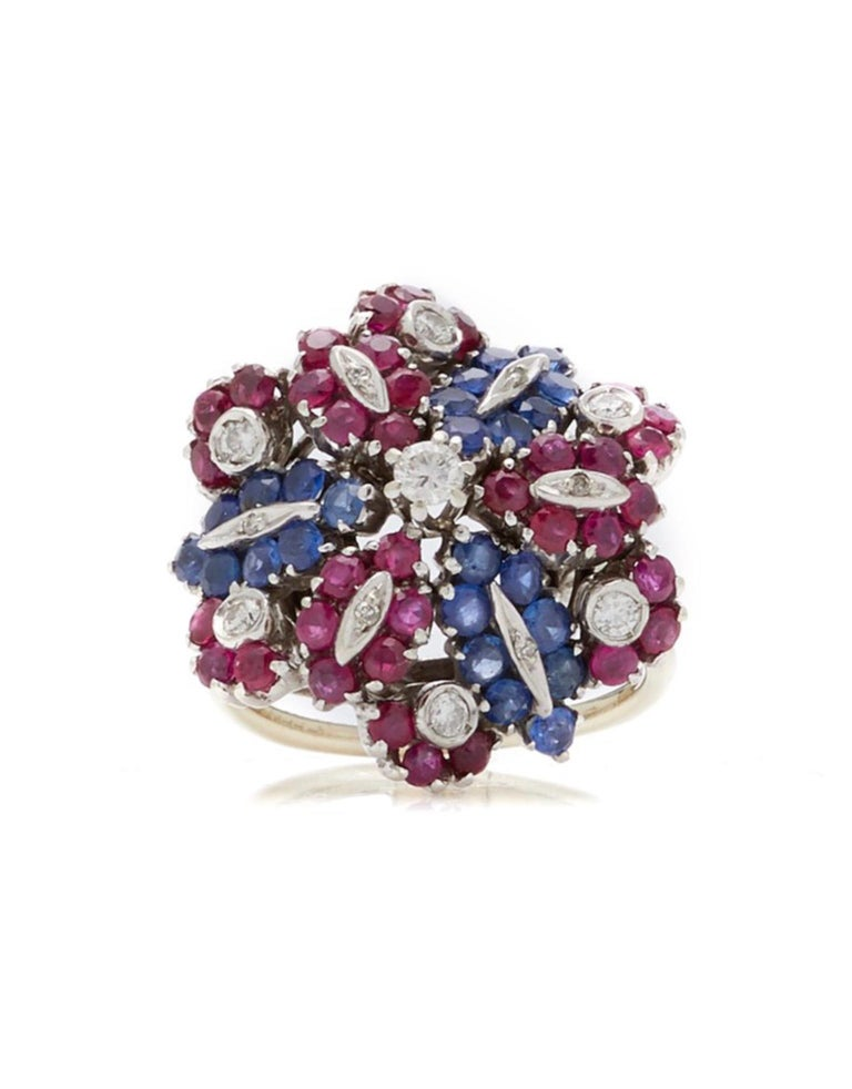 A chic retro flower ring embellished with rubies, sapphires, and diamonds, set in white gold.