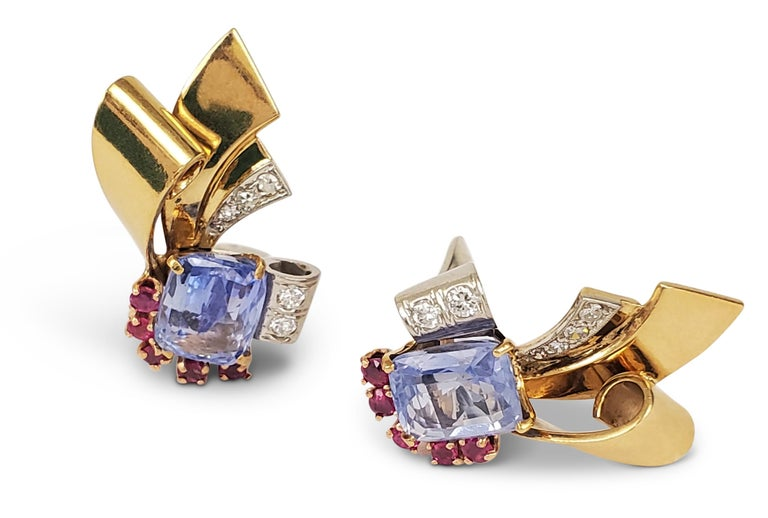 A pair of darling Retro scroll motif earrings crafted in 14 karat yellow gold and platinum. The earrings are set with pastel blue colored sapphires weighing an estimated 6.00 carats in total and flanked by 0.50 carats of rubies. The earrings are