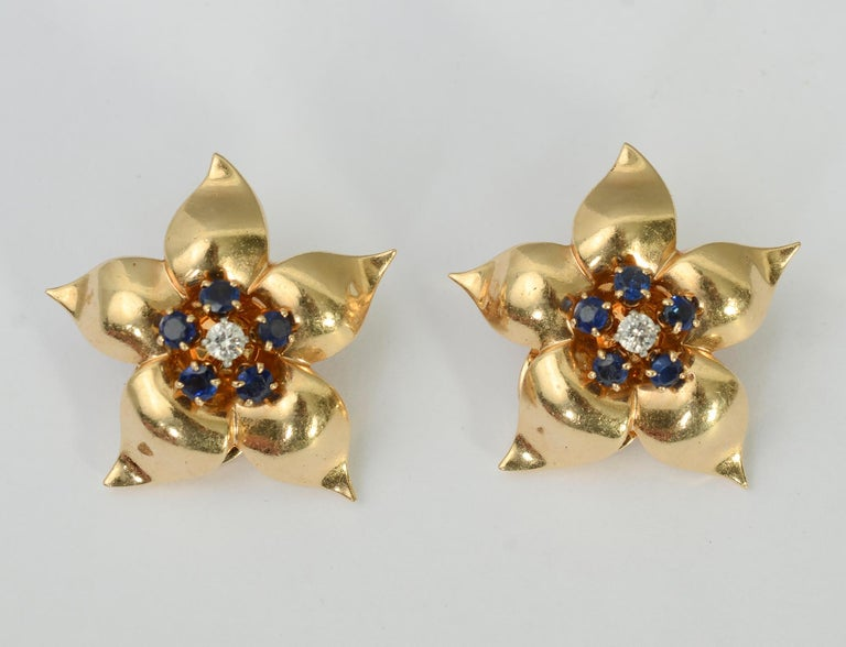 Lovely star-like flower earrings with great form and dimensionality. They are centered with a diamond around which are five sapphires. Clip backs can be converted to posts.