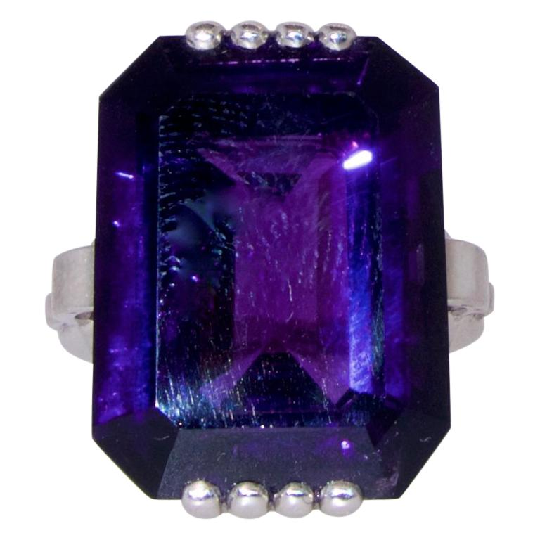 Amethyst, very fine quality,  weighing 16.82 cts, displaying a bright deep purple color with red undertones, set in a geometric hand made platinum ring.  The ring is a size 6 and can be altered easily.  Art Moderne, circa 1950