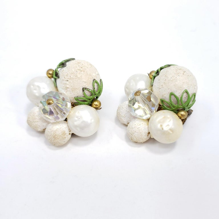 Retro chic! These vintage clip on earrings feature a cluster of textured white beads with green and brass accents.  Circa mid 1900s. Brass-tone.