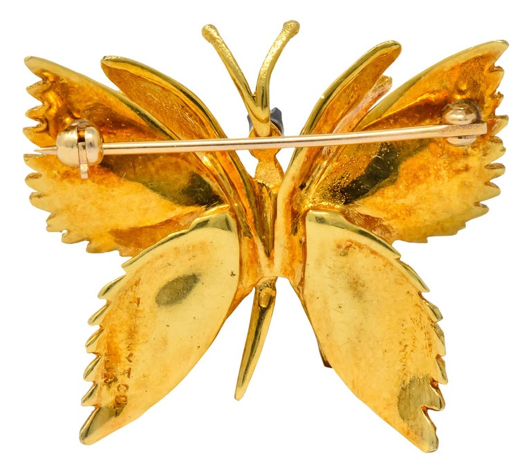 Featuring a sculptural butterfly with open wings  Accented by a round brilliant cut diamond weighing approximately 0.03 carat, eye-clean and white  With pin-stem and locking closure  Fully signed Tiffany & Co and stamped 18k (worn)  Measures: 1 x 1