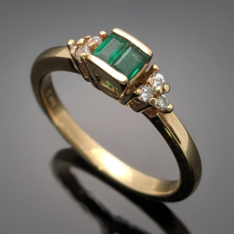 This is a stunning vintage 14kt yellow gold ring featuring two emeralds at an estimated 0.16 cttw. and six diamonds estimated 0.06 cttw. Estimated weight of gold is 2 gr.   We will size it for you.