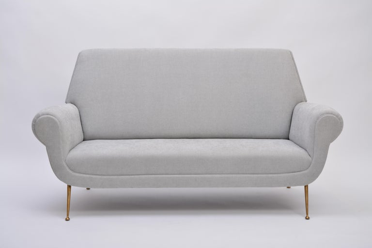 Reupholstered Grey Italian Mid-Century Modern sofa by Gigi Radice for Minotti  This sofa was designed by Gigi Radice for Minotti in the 1950s. It has been upholstered and features brass legs. It is in excellent vintage condition.