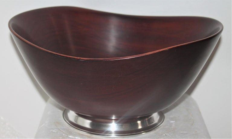 Large salad bowl with sterling silver base signed sterling. This midcentury mahogany salad bowl is in fine condition with a nice heavy sturdy base.