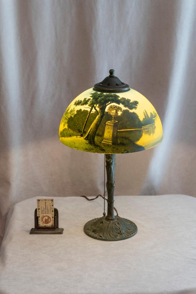 This reverse painted table lamp we know to be produced by Phoenix. It is on the original base and also has the original heat cap and finial. This lamp is so original, that no one ever thought to remove the paper label on the inside of the shade that