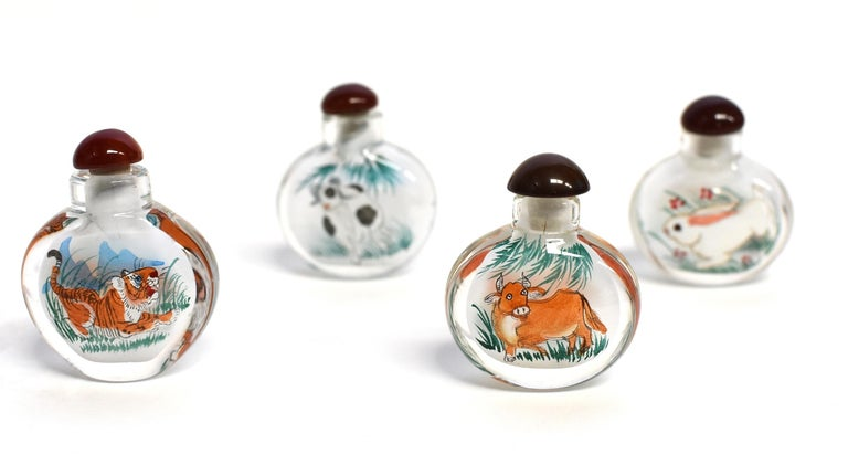 Our snuff bottles are topped with gemstone grade agate lids and 100% hand painted from within. The Chinese art of églomisé uses a very thin bamboo brush with a few strands of hair to apply watercolor on the inside walls of the blank glass bottle
