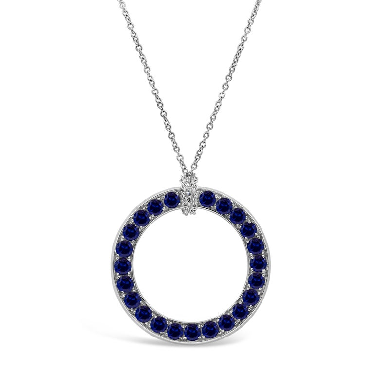 A unique circle pendant showcasing round brilliant diamonds weighing 1.60 carats total on one side, and reverses to round blue sapphires weighing 1.80 carats total on the other side. Made in 18 karat white gold. Attached to an 18 inch white gold