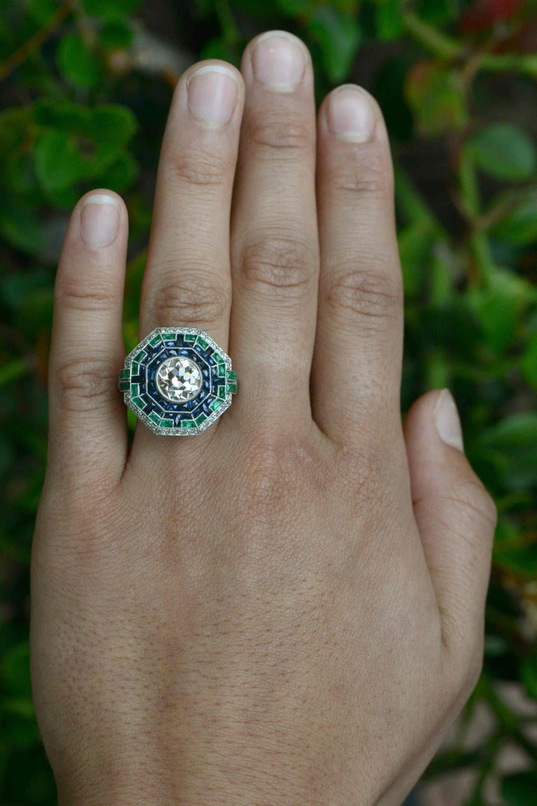This revivalist Art Deco Style 2 carat diamond cocktail ring explodes with a shower of emeralds and sapphires that glow upon your hand. As an engagement ring, anchored by a significant antique diamond weighing 2.15 carat. The chunky facets of the