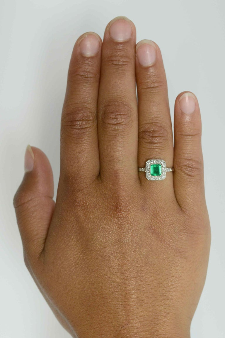 A breathtaking grass-green Colombian emerald takes center stage in this striking Art Deco Style engagement ring. The platinum setting features a 3/4 carat gemstone that glows with a light from within its soul. Floating in a bezel setting and