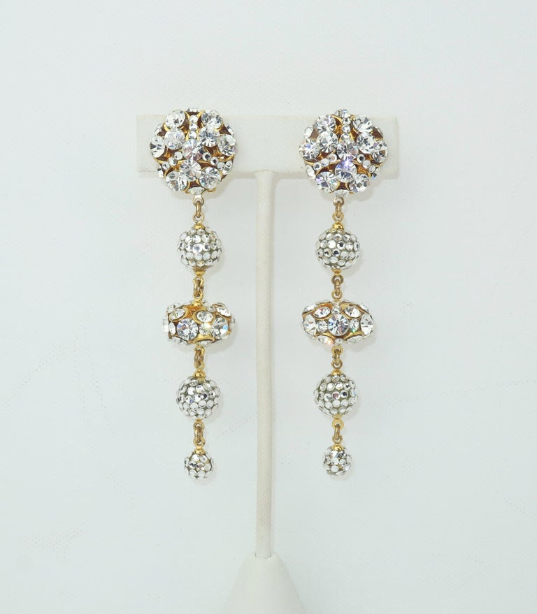 Dazzling and delightful!  These C.1980 clip on gold tone earrings sparkle with dangling orbs embellished by rhinestones and pave crystals.  Beautifully made and in very good condition with the hint of adhesive remnants from old earring pads to the