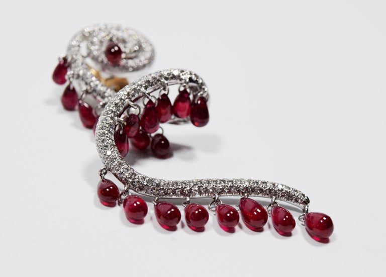 A pair of stunning rhodium plated gold, ruby and diamond earrings of spiral design containing 42 polished ruby briolettes and numerous round brilliant cut diamonds weighing approximately 4.30 carats total, with 18 karat yellow gold posts and clip