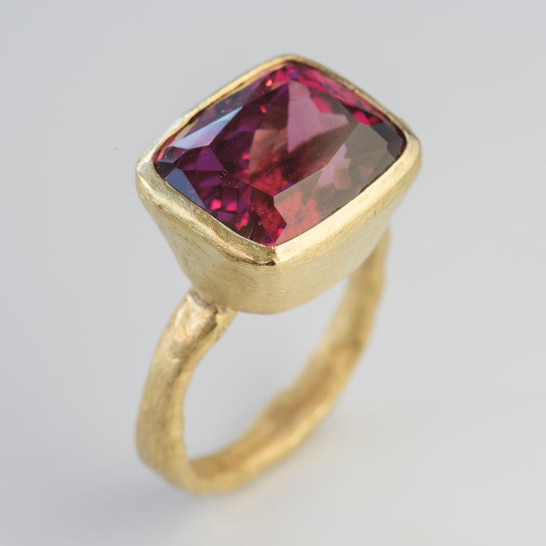 18k yellow gold organic textured ring with stunning Rhodolite Garnet, rectangular cushion cut 13.78 carats. The colour of this Rhodolite Garnet is rich and vibrant, flashing scarlet, fuchsia and raspberry depending on the light.  Disa Allsopp is