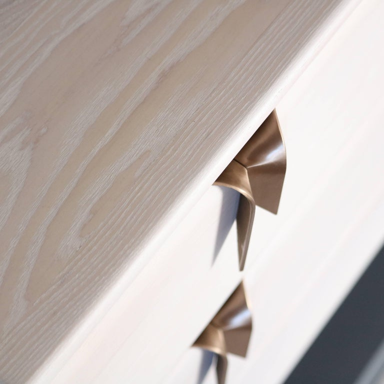 An interest in the translation of textile languages and soft surfaces through furniture forms has led to the development of a unique hardware and storage collection. Inspired by ribbons and communicated through hand cast solid bronze hardware and