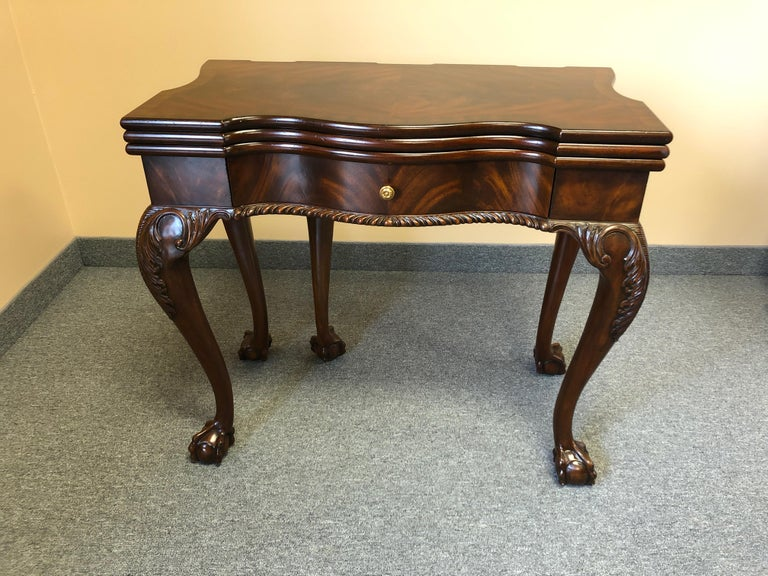 A beautifully made game table by Maitland-Smith with a variety of looks and uses. One surface is a rich flame mahogany inlaid game table for checkers, backgammon or checkers. A second top folds over to replace the game table with a sumptuous tooled