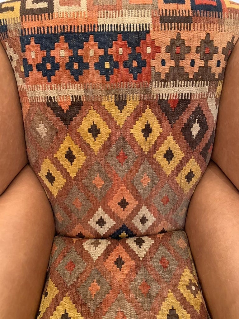 """Handsome vintage wingback chair in new leather and vintage Kilim upholstery. The chair has mahogany legs and ball and claw feet. Measures: Seat 22"""" D x 18.5"""" H."""