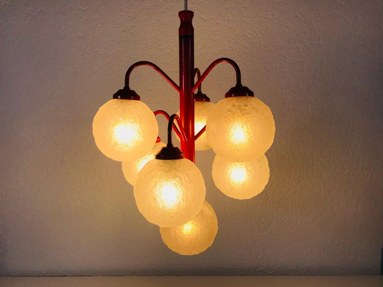 A Richard Essig chandelier made in Germany in the 1960s. It is fascinating with its Space Age design and six transparent balls. The body of the light is made of full metal, including the arms.  The light requires six E14 light bulbs.