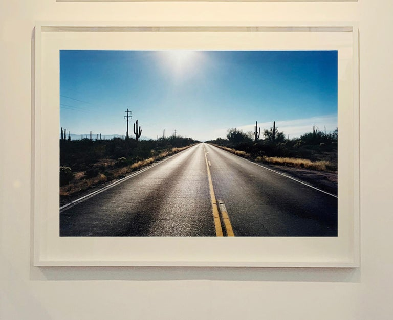Road to Gunsight, part of Richard Heeps 'Dream in Colour' Series, this is the classic American open road photograph, which is a metaphor of a journey throughout Richard's work. The early morning sunlight in the big blue sky and the road combine to