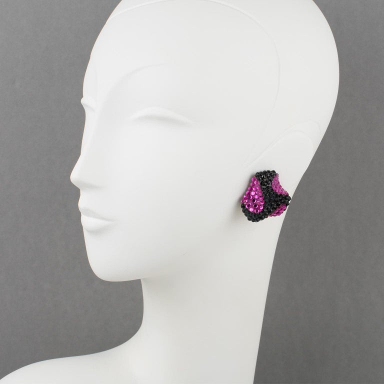Stunning statement clip-on earrings designed by Richard Kerr in the 1980s. They are made up of his signature pave rhinestones. Featuring dimensional triskelion shape all covered with colorful crystal rhinestones on a black resin background frame.