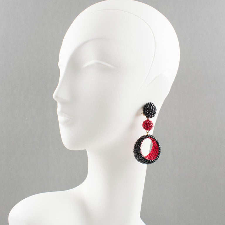 Fancy clip-on earrings designed by Richard Kerr in the 1980s. They are made up of his signature pave rhinestones. Featuring oversized dangle shape with bead and asymmetric dimensional donut all covered with red and black crystal rhinestones on black
