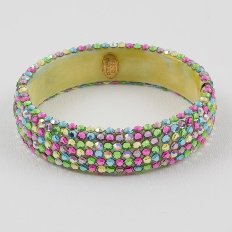 Fabulous statement clamper bracelet designed by Richard Kerr in the 1980s. it is made up of his signature pave rhinestones. Featuring a large band shape all covered with multicolor crystal rhinestones. Assorted tutti frutti pastel colors of jonquil
