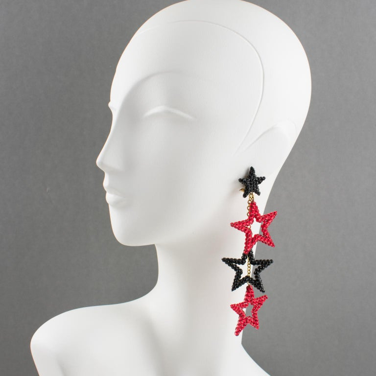 Handsome chandelier clip-on earrings designed by Richard Kerr in the 1980s. They are made up of his signature pave rhinestones. Featuring shoulder-duster shape with three stars shaped dangling charms all covered with red and black crystal