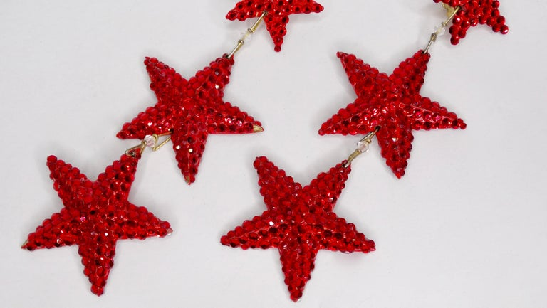 The most divine pair of Richard Kerr rhinestone earrings from the 1980s! Earrings feature three red rhinestone embellished stars with clip on backs. Stamped Richard Kerr drops down 4 inches. The perfect accent piece to any evening or daytime look!