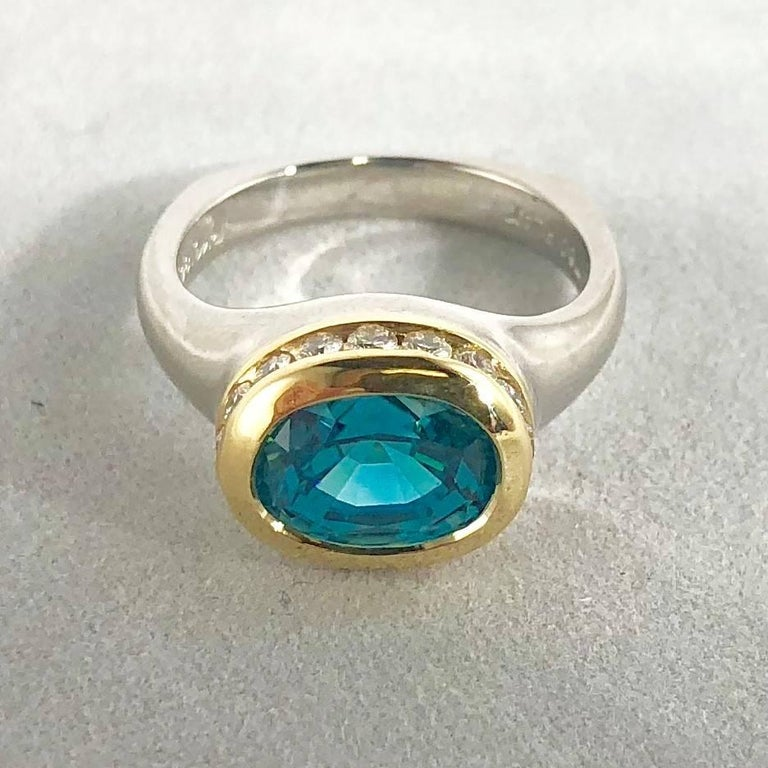 Richard Krementz Gemstones  Platinum, 18 karat and 5.48 carat Blue Zircon and Diamond cocktail ring. This piece is created in a two tone Platinum and 18 karat yellow gold weighing 11.7 grams/ 7.5 dwt. The center stone is an Oval cut Blue Zircon