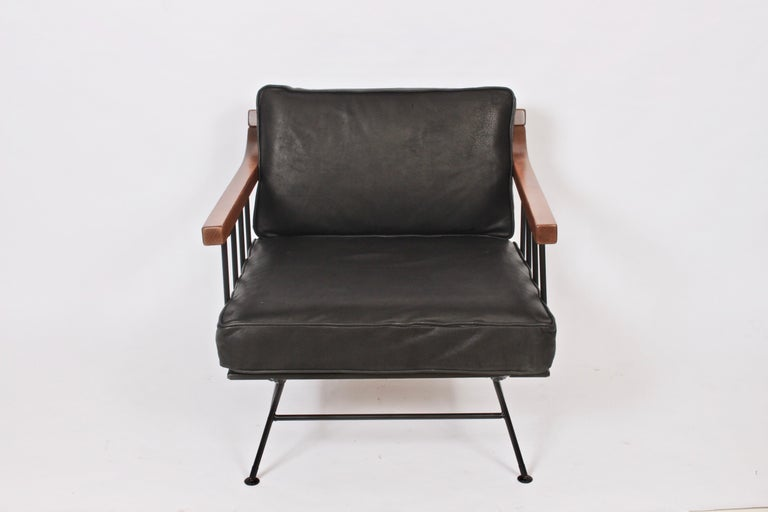 Richard McCarthy for Selrite lounge chair, 1950s. Featuring a Wrought Iron framework, Elm armrests, newly upholstered distressed Black Leather removable and reversible cushions, burlap center support and splayed legs detailed with capped feet.