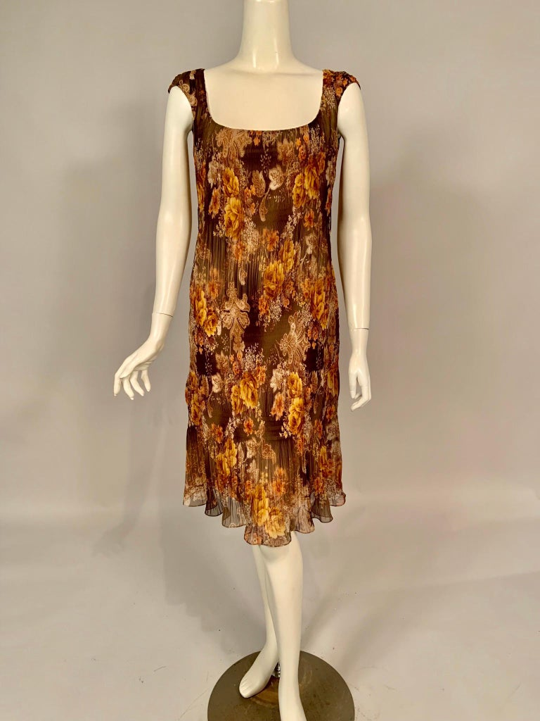Richard Tyler has chosen an interesting micro pleated autumnal silk chiffon for this chic cocktail dress. This gives the dress enough room to just slip on over your head. It has a rounded, scoop neckline and cap sleeves. It is fully lined in   a