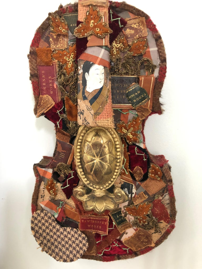 A rich mixed-media collage on an antique violin having meticulously layered paper ephemera with a Japanese motife, leather book bindings, bits and pieces from a crazy quilt, vintage trimmings and tin cutout. A splendid wall sculpture in brown, gold,