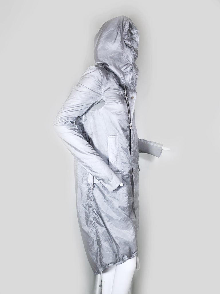 A rare and sporty silver satin military-inspired mid-calf length hooded raincoat with zip down front and snap flap. Arms are fitted with an elasticized panel from cuff to underarm. Drawstring bottom hem. Fits US size 2-4. Condition: Next to new.
