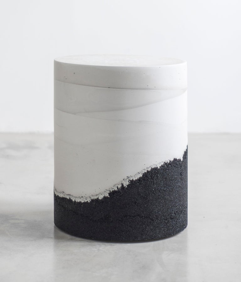 Composed in a language of landscape-oriented abstraction, the made-to-order drum is cast from hand-dyed white cement and black silica. Poured by hand over the black granules, the white cement combines the materials to create an effect evocative of a