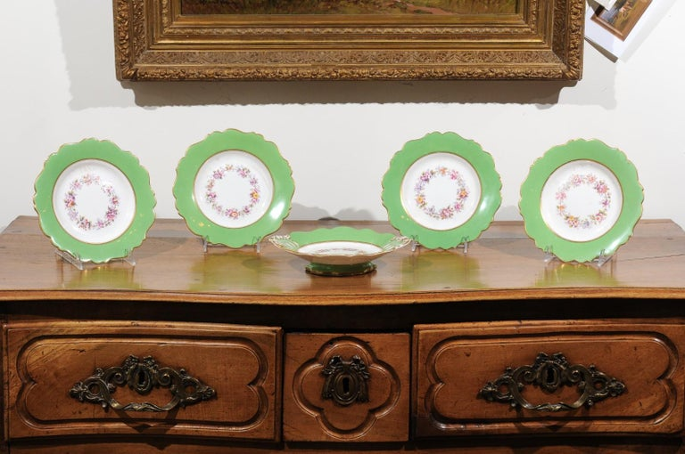 Four Ridgway porcelain hand painted dinner plates and one compote from the 19th century, with green rim and floral decor, priced and sold separately. Born in England during the 19th century, each of these Ridgway porcelain pieces features a lovely