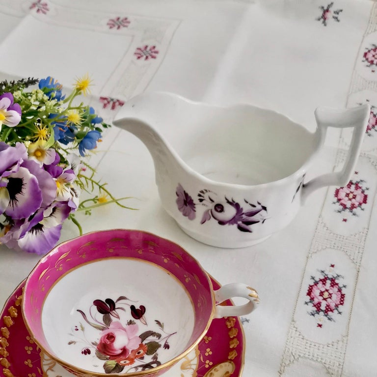 This is a charming milk jug or creamer made circa 1825 by Ridgway. The jug is decorated with simple monochrome puce / purple flowers on a white ground. The shape is typical for its time and Ridgway called it the